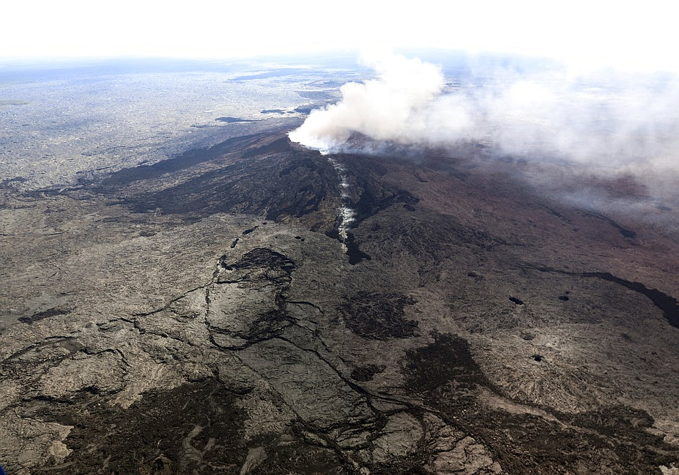 In this photo released by U.S. Geological Survey, ash plume rises above the Puu Oo crater, on Hawaii's Kilaueaa Volcano Thursday, May 3, 2018 in Hawaii Volcanoes National Park. Nearly 1,500 residents were ordered to evacuate from their volcano-side homes after Hawaii's Kilauea Volcano erupted, sending molten lava to chew its way through forest land and bubble up on paved streets. (U.S. Geological Survey via AP)