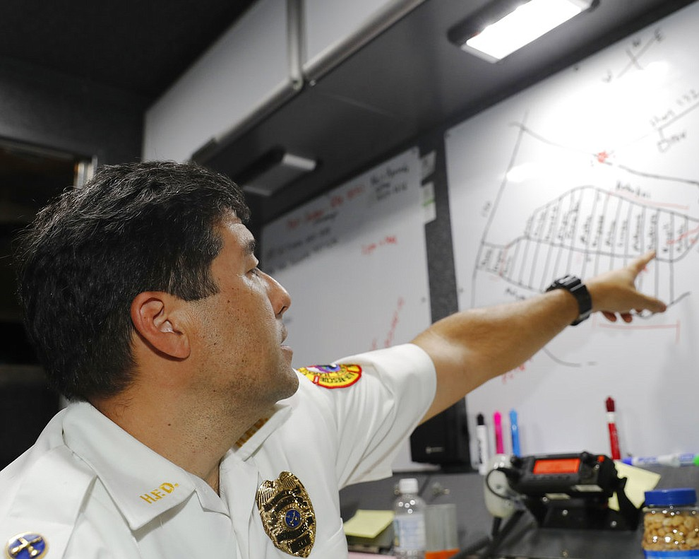 CORRECTS SPELLING FROM LELANI TO LEILANI -Hawaii Fire Department battalion chief Darwin Okinaka points to a map where recent volcanic eruptions have occurred on Friday, May 4, 2018, at Leilani Estates in Pahoa, Hawaii. Civil defense has set up a command center at the entrance to the subdivision, and authorities have ordered a mandatory evacuation. (AP Photo/Marco Garcia)