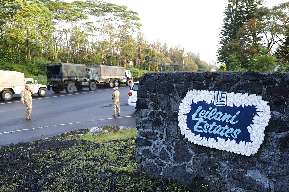 National guardsmen and police stand at the entrance to Leilani Estates, Friday, May 4, 2018, in Pahoa, Hawaii. A mandatory evacuation for the area as declared by the state. Due to unsafe conditions in the area from the recent lava eruption, residents who evacuated could not return to their homes Friday. (AP Photo/Marco Garcia)