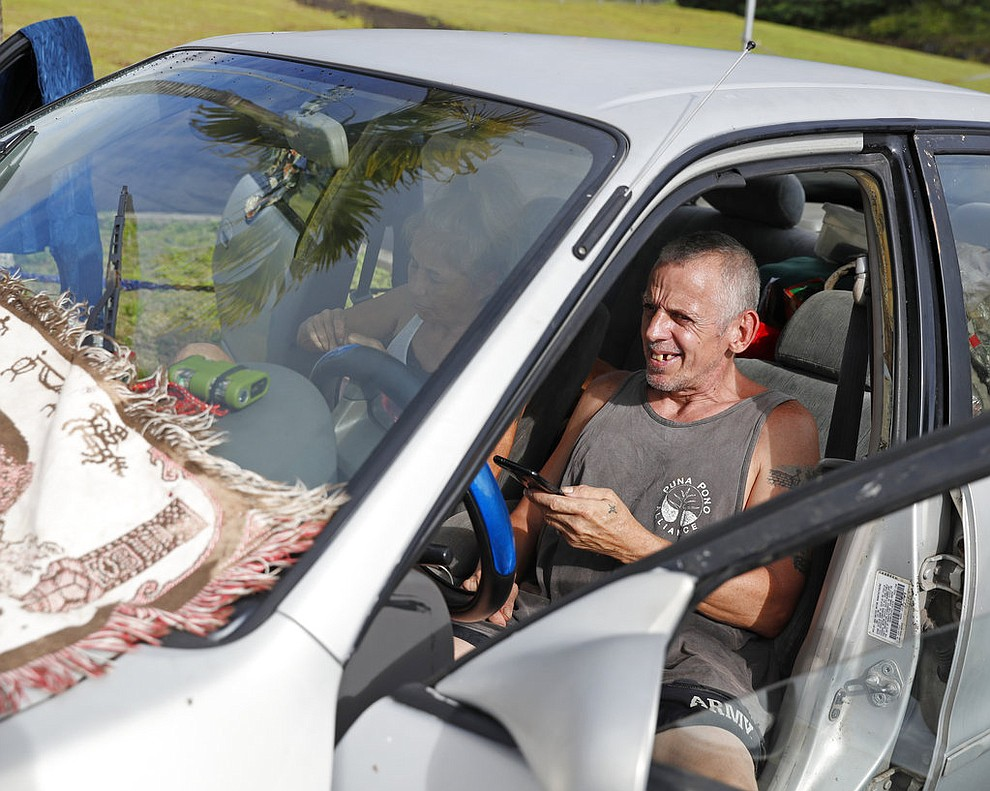 Mary Hicks, 56, left, and Tim Hicks, 51, both residents of the Leilani Estates, spent the night in their car after being evacuated from their home due to a lava eruption, Friday, May 4, 2018, in Pahoa, HI. (AP Photo/Marco Garcia)