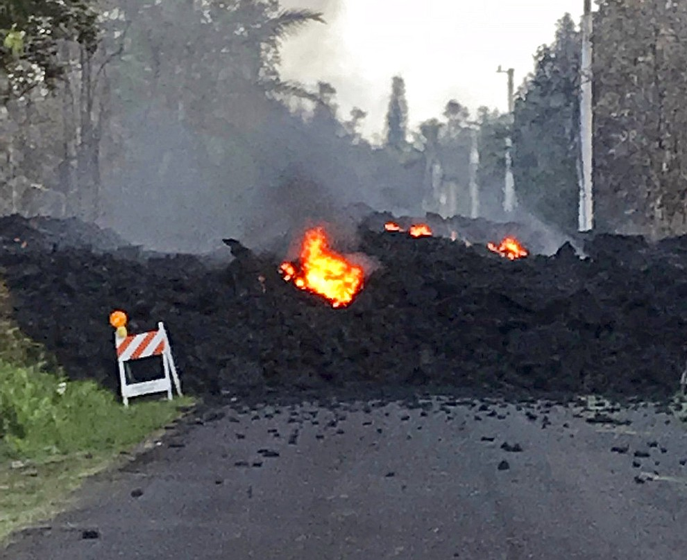 """This photo provided by Hawaii Electric Light shows lava flowing over Mohala Street in the Leilani Estates area near Pahoa on the Big Island of Hawaii Friday, May 4, 2018. Nearly 1,500 people have fled from their homes after Hawaii's Kilauea volcano sent molten lava chewing through forests and bubbling up on paved streets in an eruption that one resident described as """"a curtain of fire."""" (Hawaii Electric Light via AP)"""