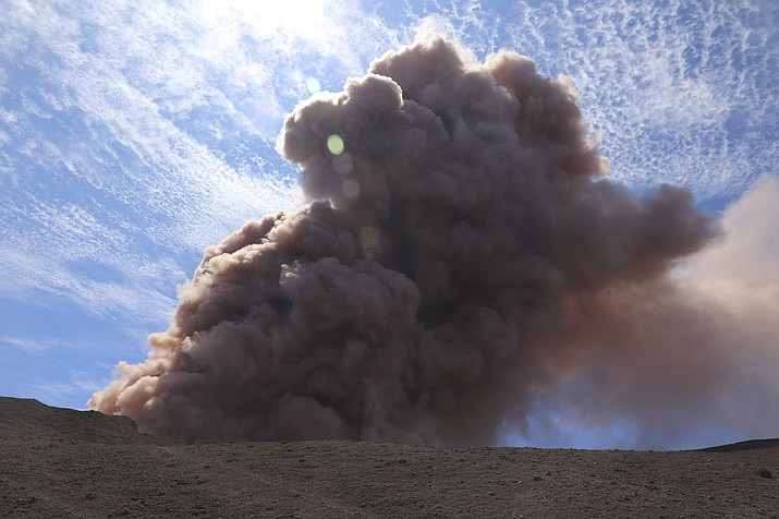 In this photo released by U.S. Geological Survey, a plume of ash rises from the Puu Oo vent on Hawaii's Kilaueaa Volcano after a magnitude 5.0 earthquake, Thursday, May 3, 2018 in Hawaii Volcanoes National Park. Hawaii's Kilauea volcano erupted Thursday, sending lava shooting into the air in a residential neighborhood and prompting mandatory evacuation orders for nearby homes. Hawaii County said steam and lava poured out of a crack in Leilani Estates, which is near the town of Pahoa on the Big Island. (U.S. Geological Survey)