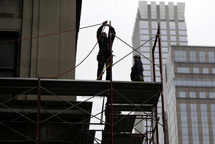 In this Feb. 20, 2018, file photo, construction workers work in midtown Manhattan in New York. U.S. productivity grew at an annual rate of 0.7 percent in the first three months of 2018, a weak reading but a slight improvement from the previous quarter.(AP Photo/Seth Wenig, File)