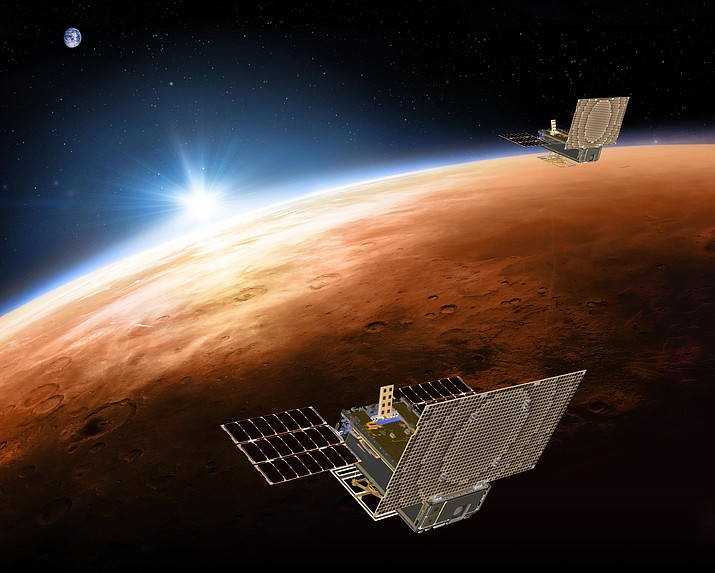 This illustration made available by NASA on March 29, 2018 shows the twin Mars Cube One (MarCO) spacecraft flying over Mars with Earth and the sun in the distance. The MarCOs will be the first CubeSats - a kind of modular, mini-satellite - flown into deep space. They're designed to fly along behind NASA's InSight lander on its cruise to Mars. (NASA/JPL-Caltech via AP)