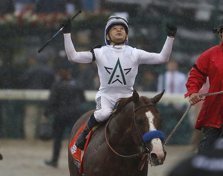 Mike Smith celebrates after riding Justify to victory during the 144th running of the Kentucky Derby horse race at Churchill Downs Saturday, May 5, 2018, in Louisville, Ky. (AP Photo/Jeff Roberson)