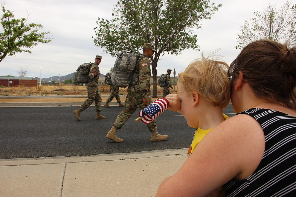 Robbie Garcia wipes tears from his eyes when he sees his dad, Robert Garcia (waving), walking away with National Guard Infantry Unit Charlie Company 1st Battalion-158 during a deployment parade held in Prescott Valley on Sunday, May 6, 2018. (Max Efrein/Daily Courier)