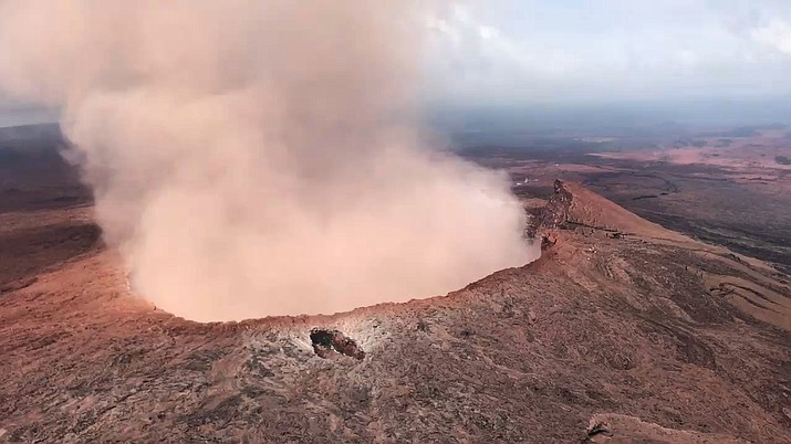 In this Saturday, May 5, 2018 photo provided by U.S. Rep. Tulsi Gabbard, who is on active duty Hawaii National Guard deployment, ash from the Puu Oo vent on Kilauea volcano rises into the air, near Pahoa, Hawaii. Hawaii's erupting Kilauea volcano has destroyed homes and forced the evacuations of more than a thousand people. (U.S. Rep. Tusli Gabbard/National Guard)