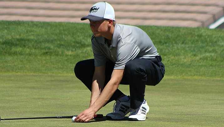 Kingman Academy's Jake Scott places his ball for a putt at Cerbat Cliffs Golf Course earlier this season. Scott, a sophomore, has earned a spot in the D-III State Championship tournament. (Daily Miner file photo)