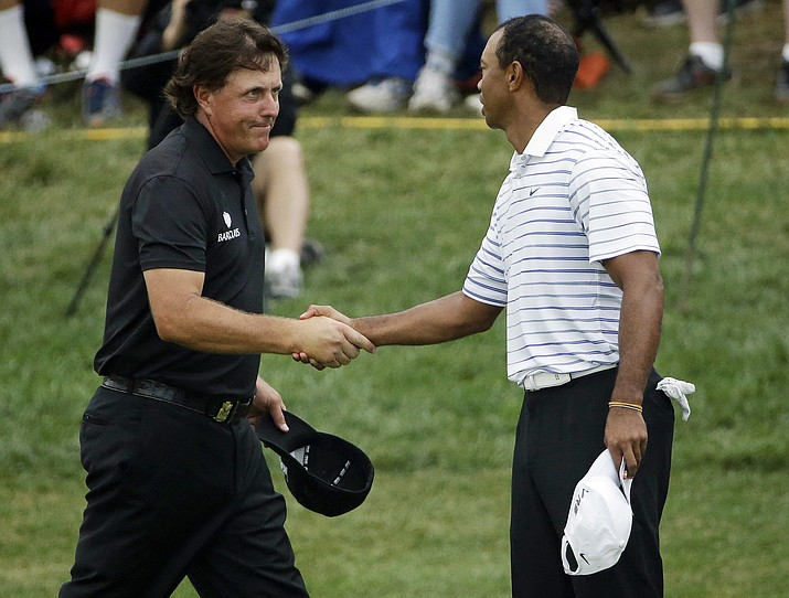 In this Aug. 8, 2014, file photo, Phil Mickelson, left, shakes hands with Tiger Wood after the second round of the PGA Championship golf tournament at Valhalla Golf Club in Louisville, Ky. Woods and Mickelson are in the same group at The Players Championship this week.   (AP Photo/David J. Phillip, File)
