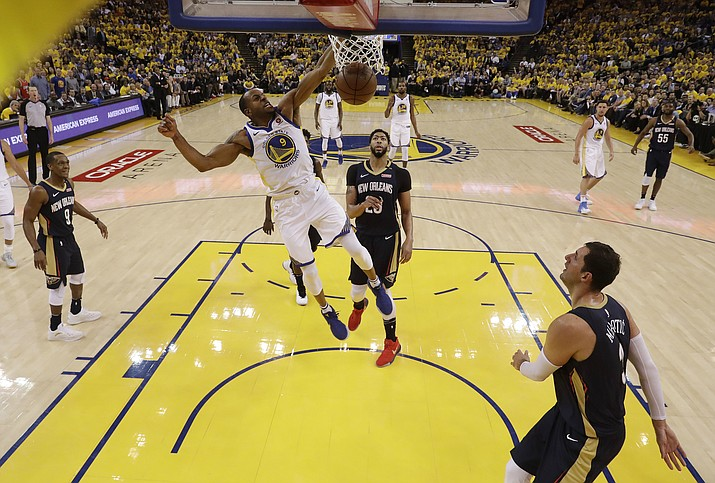 Golden State Warriors' Andre Iguodala (9) dunks past New Orleans Pelicans' Anthony Davis, center, during the first half in Game 5 of an NBA basketball second-round playoff series Tuesday, May 8, 2018, in Oakland, Calif. (AP Photo/Marcio Jose Sanchez)