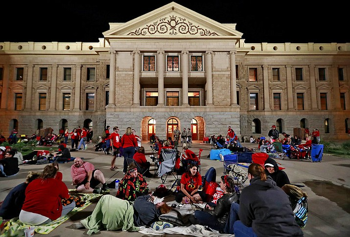 Teachers camp out as the Arizona legislature debates a budget negotiated by majority Republicans and GOP Gov. Doug Ducey Thursday, May 3, 2018, at the Capitol in Phoenix. The budget gives teachers big raises but falls short of their demands for better school funding. (AP Photo/Matt York)