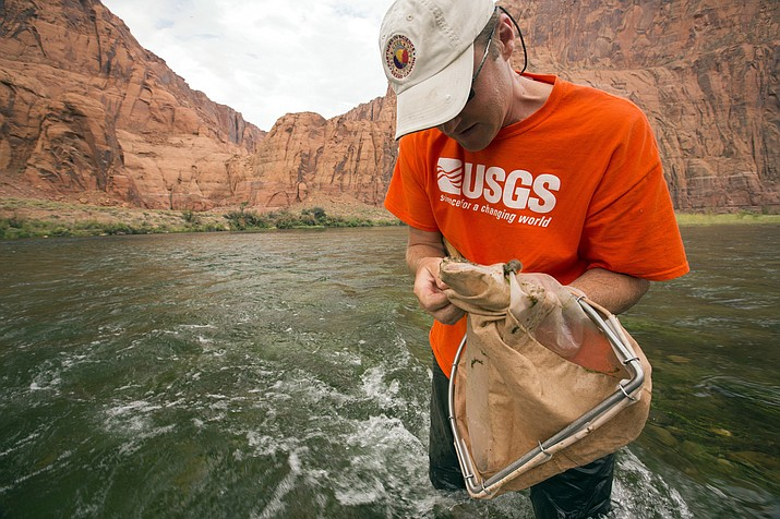 In this July 10, 2013 photo, U.S. Geological Survey scientist Ted Kennedy takes aquatic samples in the Colorado River below Glen Canyon Dam in northern Arizona. Aquatic insects serve as food for fish, bats and birds in the Grand Canyon. (David Herasimtschuk/ Freshwaters Illustrated/USGS via AP)