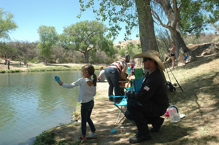 Central Arizona Fire and Medical Authority Engineer Mike Huddleston watches his daughter Alana Huddleston cast her fishing pole at the Badges & Bobbers event at Fain Lake Saturday, May 5. Designed to teach kids fishing, the goal was to get kids hooked on the sport rather than drugs and crime. (Jason Wheeler/Courier)