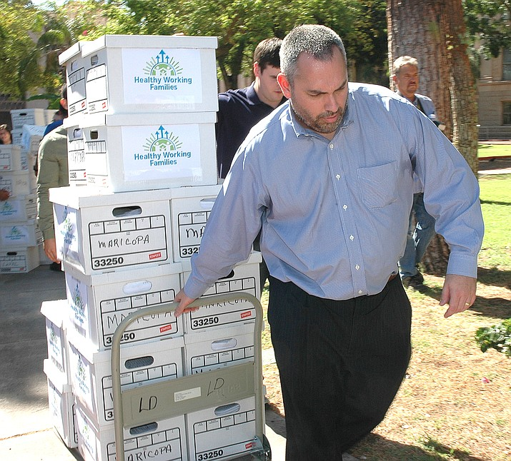 An unidentified man wheels in signed initiative petitions in Maricopa County. Howard Fischer/Courtesy