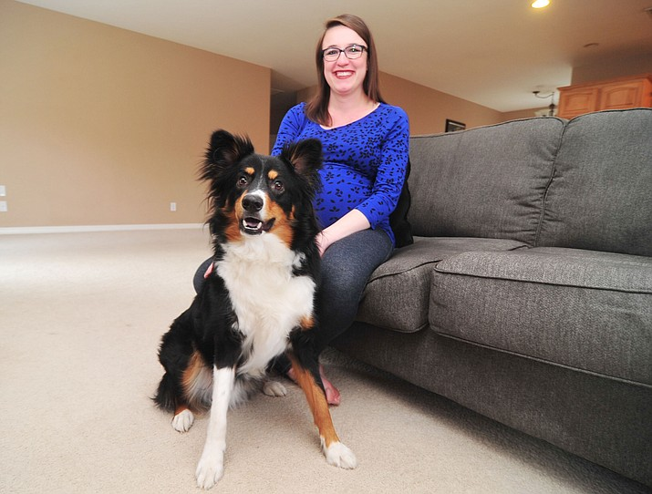 Amelia Lundgren and her dog Barney pose in their Prescott Valley home Wednesday May 2, 2018. Barney suffered a sezure and a Prescott Valley Animal Control officer helped get Barney to a veteranarian because Lundgren is 9 months pregnant. (Les Stukenberg/Tribune)