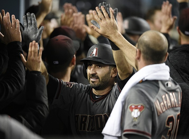 Arizona Diamondbacks' Daniel Descalso, center, celebrates with the dugout after hitting the go-ahead three-run home run during the 12th inning of a baseball game against the Los Angeles Dodgers in Los Angeles, Tuesday, May 8, 2018. (Kelvin Kuo/AP)