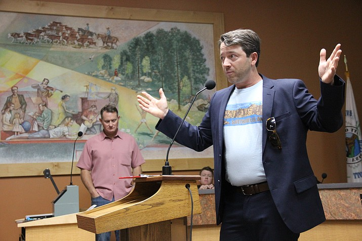 Joe Trudeau, Chairman of Save The Dells, a group committed to preserving the Granite Dells in Prescott, speaks to a public assembly at the Prescott City Council chamber Tuesday night, May 8, about a proposed development of land both near the Prescott airport and in and around the Granite Dells. The primary developer for the project, Jason Gisi, stands silently in the background as Trudeau speaks. (Max Efrein/Courier)
