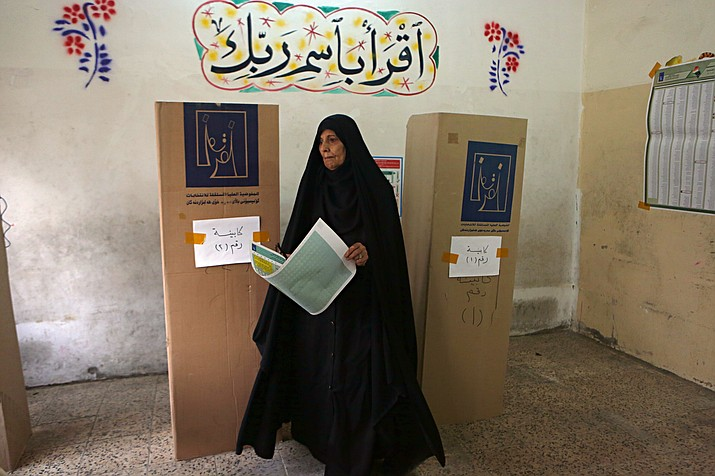 An Iraqi woman prepares to cast her vote in the country's parliamentary elections in Baghdad, Iraq, Saturday, May 12, 2018. Polls opened across Iraq on Saturday in the first national election since the declaration of victory over the Islamic State group. (AP Photo/Khalid Mohammed)