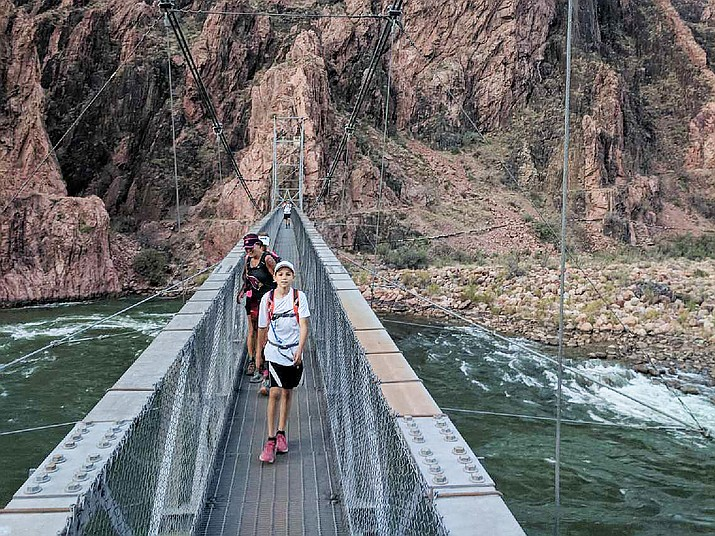 Talen Pitterle of Dewey, 11, crosses the footbridge over the Colorado River on his one-day trek from rim-to-rim-to-rim of the Grand Canyon in April. He may be the youngest to accomplish the feat. (Courtesy)