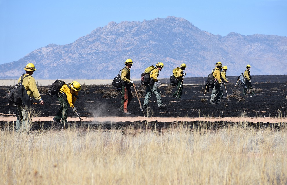 On the morning of May 12, 2018, fire crews walk in a line mopping up after the Viewpoint Fire in the Poquito Valley area of Prescott Valley, Arizona. (Richard Haddad/WNI)
