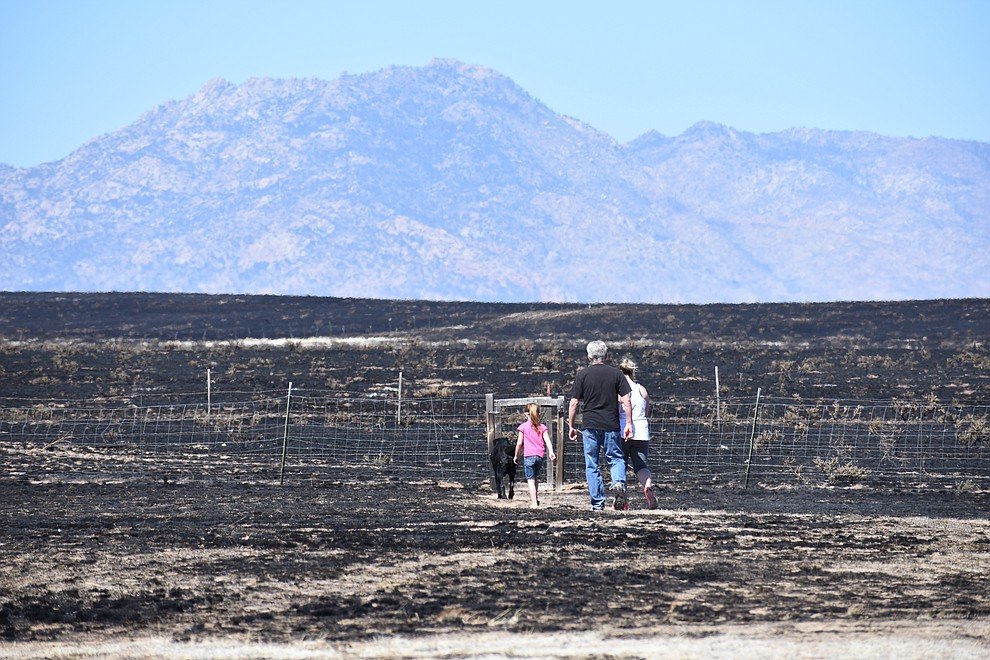 On the morning of May 12, 2018, a family walks out to the edge of the burn area of the Viewpoint Fire  near the 7000 block of Whisper Ranch Road in the Poquito Valley community of Prescott Valley, Arizona. (Richard Haddad/WNI)