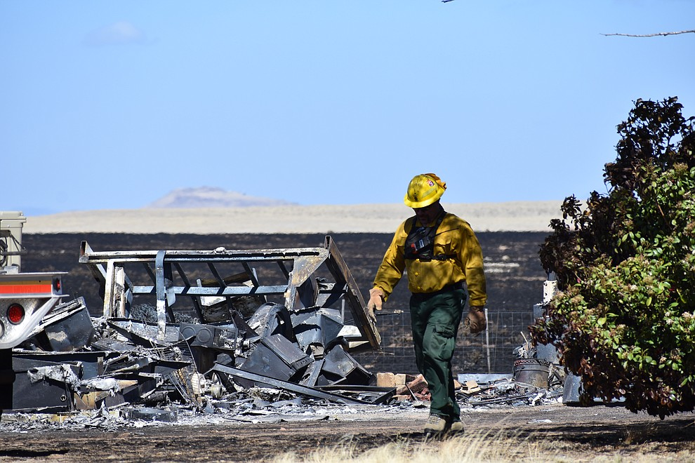 On the morning of May 12, 2018, a firefighter walks along the property line of a home that was destroyed by the Viewpoint Fire in the Poquito Valley community of Prescott Valley, Arizona. (Richard Haddad/WNI)