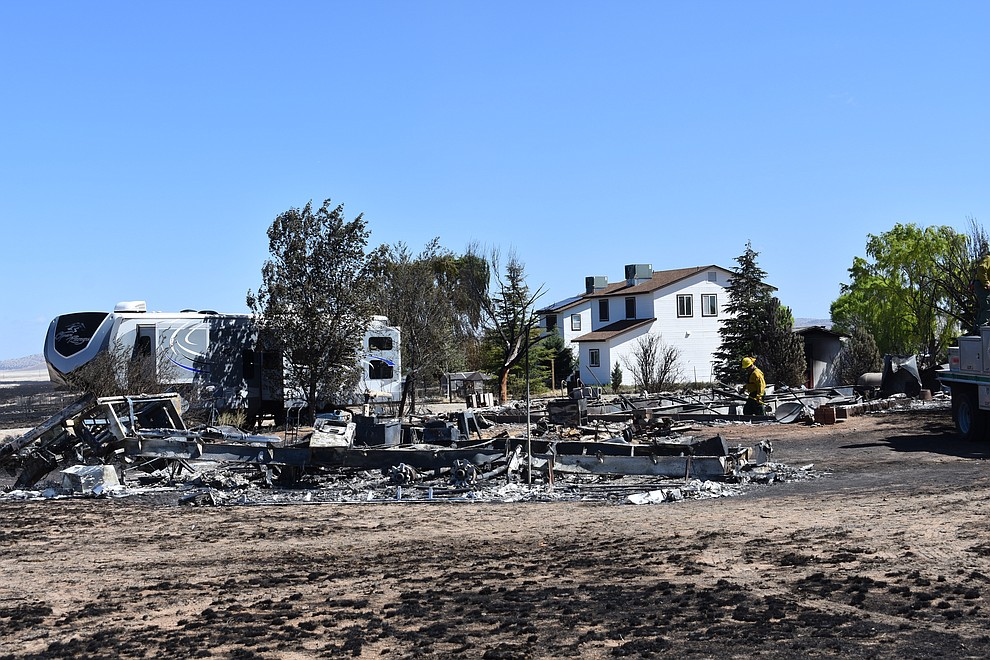 On the morning of May 12, 2018, a firefighter puts out hot spots on a home destroyed a day earlier by the Viewpoint Fire in the 7000 block of Whisper Ranch Road in the Poquito Valley community of Prescott Valley, Arizona. (Richard Haddad/WNI)