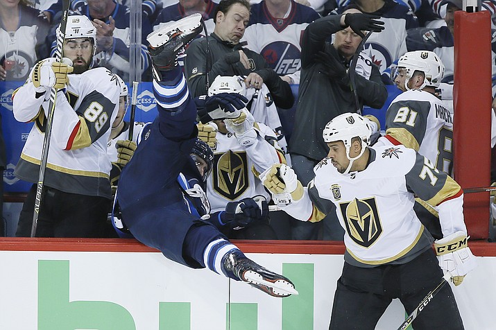 Winnipeg Jets' Blake Wheeler gets dumped over the boards by Vegas Golden Knights' Ryan Reaves (75) during the first period of Game 1 of the NHL hockey playoffs Western Conference final, Saturday, May 12, 2108, in Winnipeg, Manitoba. (John Woods/The Canadian Press, via AP)