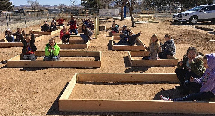 Del Rio School children sit inside planter boxes built by Lowe's Home Improvement employees in Prescott. (Courtesy)