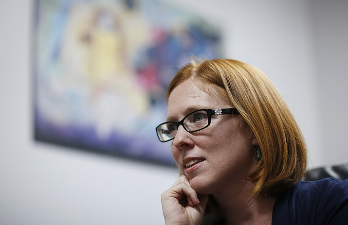 "In this May 7, 2018, photo, UNLV associate professor Sheila Bock speaks the with the Associated Press at her office in Las Vegas. Bock has been researching how and why students decorate their caps and says the themes over the years have become increasingly political. From ""Game of Loans, interest is coming"" to ""Si Se Puede, Here To Stay,"" graduating college students are choosing to decorate their graduation caps, pushing against the formality of ceremonies and taking a stand on an issue before the thousands watching them cross the stage. (AP Photo/John Locher)"
