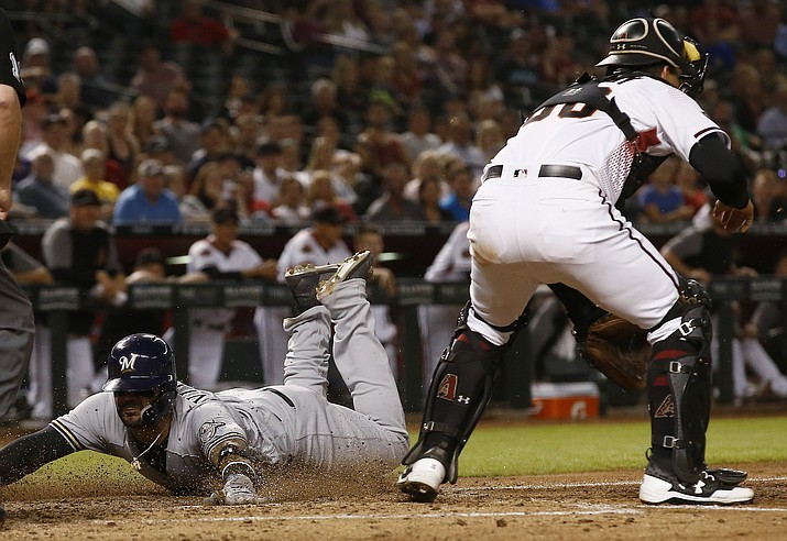 Milwaukee Brewers' Jonathan Villar, left, slides in to touch home plate to score a run as Arizona Diamondbacks catcher John Ryan Murphy, right, waits for a late throw during the seventh inning of a baseball game, Monday, May 14, 2018, in Phoenix. (AP Photo/Ross D. Franklin)