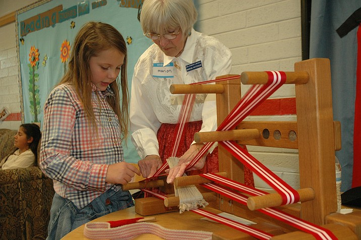 Del Rio Elementary School Fourth Grader Estara Hofer works on a small loom with Mountain Spinners & Weavers member Marion Patterson at Del Rio Elementary School's Arizona Day for fourth graders Thursday, May 10. (Jason Wheeler/Review)