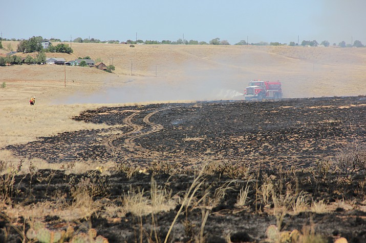 A Central Arizona Fire and Medical Authority vehicle sprays down the containment line surrounding a wildland fire that ripped through dry grassland just south of Fain Road in Prescott Valley on Monday, May 14. (Max Efrein/Courier)
