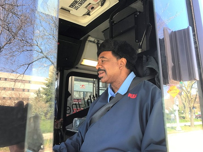 In this April 26, 2018 photo Godwin McNeal sits behind the wheel of a bus in Cleveland. McNeal has been a driver for the Greater Cleveland Regional Transit Authority for 40 years, logging an estimated 1.2 million miles without causing an accident. Officials say it's the longest preventable accident-free streak in the RTA's history. (Grant Segall/The Plain Dealer via AP)