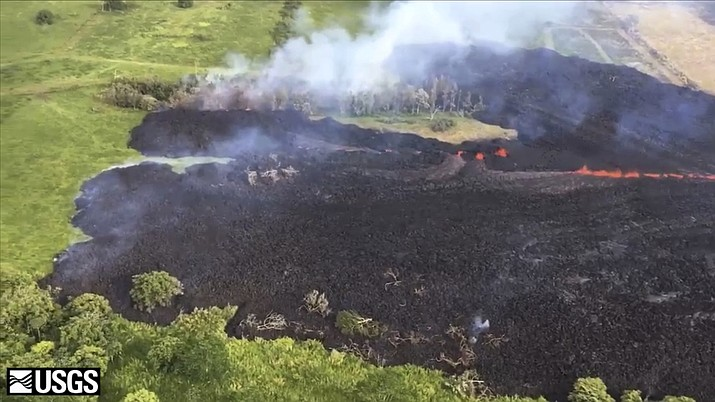 In this May 13, 2018 frame from video released by the U.S. Geological Survey, gases rise from a fissure near Pahoa, Hawaii. The new fissure sent gases and lava exploding into the air, spurring officials to call for more evacuations as residents waited for a possible major eruption at Kilauea volcano's summit. (U.S. Geological Survey)