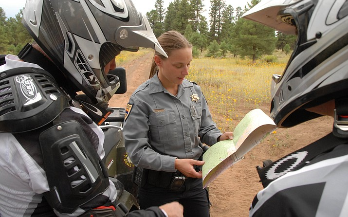 A wildlife manager with the Arizona Game and Fish Department reviews a trails map with a couple of off-highway vehicle riders. (George Andrejko, AZGFD/Courtesy)