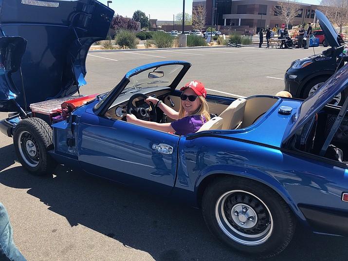 "Prescott Valley School sixth-grader Laureli Potter ""drives"" a blue car at the Arizona SciTech Fest at Embry-Riddle Aeronautical University on April 21, 2018. (Prescott Valley School/Courtesy)"