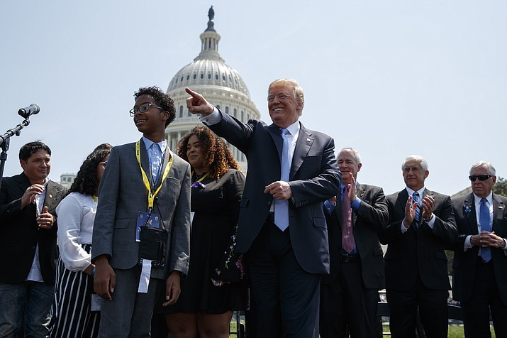 President Donald Trump points to the crowd during the 37th annual National Peace Officers Memorial Service on Capitol Hill, Tuesday, May 15, 2018, in Washington. Peter Vega, son of slain New York Police Department detective Miosotis Familia, is at left. (AP Photo/Evan Vucci)