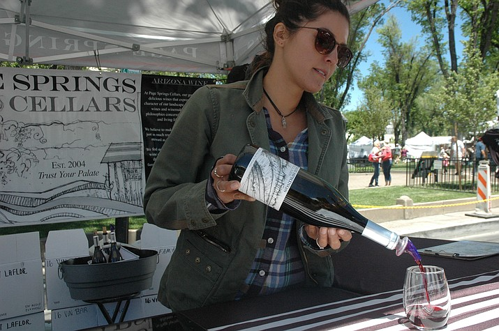 Lauren Madonado, of Page Springs Cellars, pours a glass of wine at the Mountain Artists Guild's Art & Wine Festival at courthouse plaza Saturday, May 12. (Jason Wheeler/Courier)