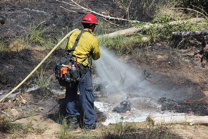Prescott Firefighter Brennan Johnstone works to extinguish the wildfire that broke out Monday morning in the city's A.C. Williams Granite Creek Park. (Cindy Barks/Courier)
