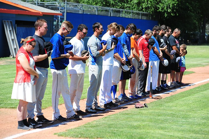 Former teammates bow their heads in a moment of silence during the third annual Wade Parker Memorial Game July 16, 2016, at Chino Valley High School. This year's memorial softball tournament, which honors Wade Parker and 18 other Granite Mountain Hotshots who died battling the Yarnell Hill Fire in 2013, will be played June 16 and 17 at Community Center Park in Chino Valley. (Les Stukenberg/Courier, file)