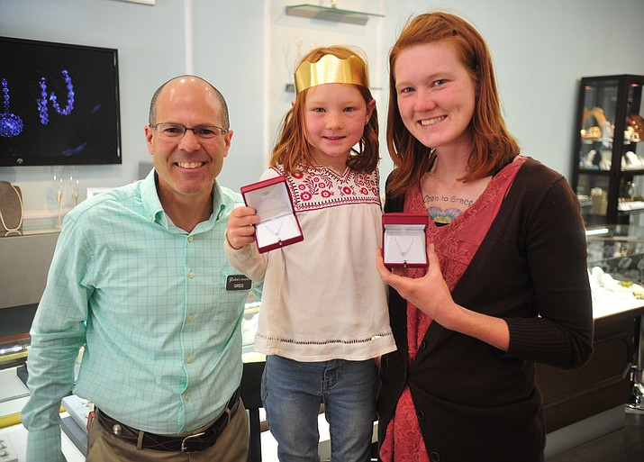 Greg Raskin, of Raskin's Jewelers, presents Ivy and Amanda Hermance -- the winners of The Daily Courier's 2018 Mother/Daughter Look-alike Contest -- with pendants Wednesday, May 16, 2018 in Prescott. (Les Stukenberg/Courier)