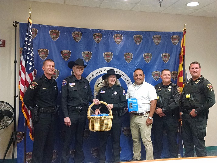 Members of the Arizona Rangers Lonesome Valley Company donate a number of cell phones to the Prescott Valley Police Department (PVPD) Family Violence Unit on Thursday, May 3, for local victims of domestic violence.