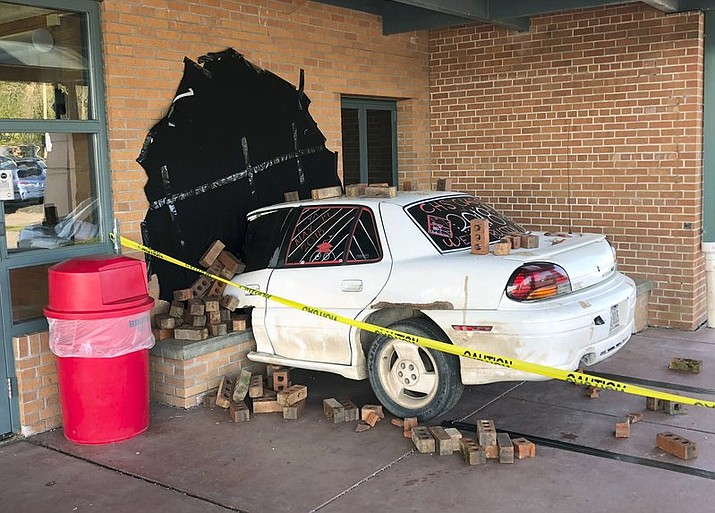 """This photo taken Wednesday, May 16, 2018, and provided by Ritchie Narges, shows what looks to be a car that crashed into the principal's office at Cumberland High School in Cumberland, Wis., but is actually an illusion created for a senior class prank. Students at the school used a junk car, some bricks, some tape and a black tarp to make it look like the car had crashed into their school. Police arrived on the scene only to realize it wasn't really a wreck. The police department wrote on Facebook that it was """"one of the best senior pranks."""" (Ritchie Narges via AP)"""