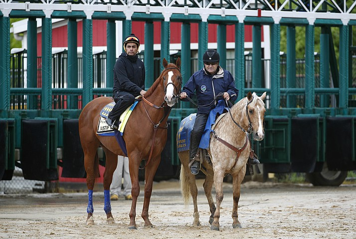 Kentucky Derby winner Justify, left, with exercise rider Humberto Gomez aboard, waits near the starting gate before being escorted to the track for a workout, Thursday, May 17, 2018, at Pimlico Race Course in Baltimore. The Preakness Stakes horse race is scheduled to take place Saturday, May 19. (Patrick Semansky/AP)