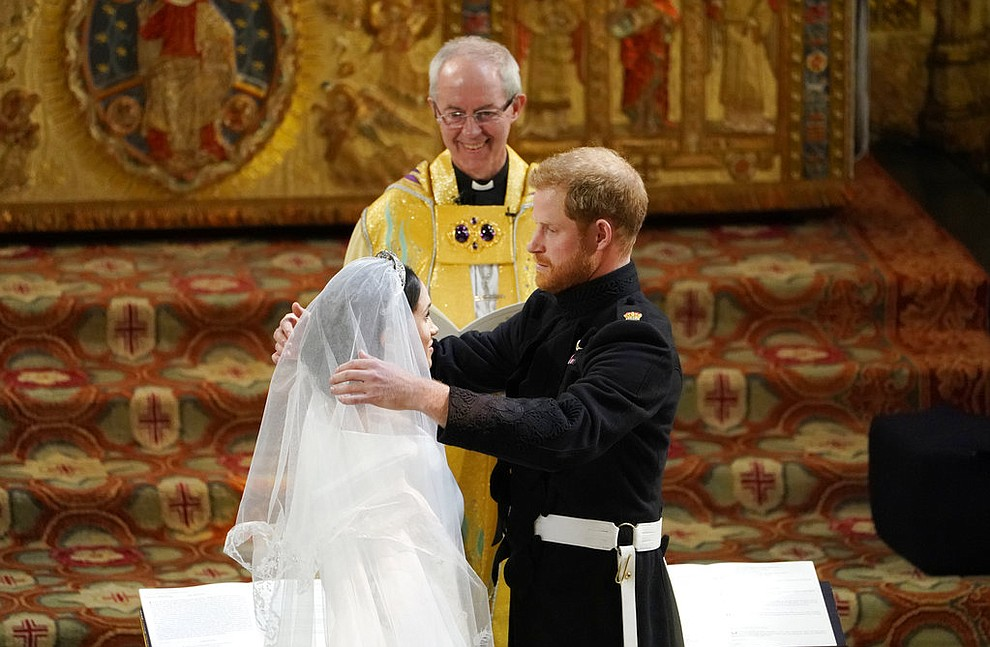Britain's Prince Harry pulls back the veil of Meghan Markle watched by Archbishop of Canterbury Justin Welby during their wedding at St. George's Chapel in Windsor Castle in Windsor, near London, England, Saturday, May 19, 2018. (Owen Humphreys/pool photo via AP)