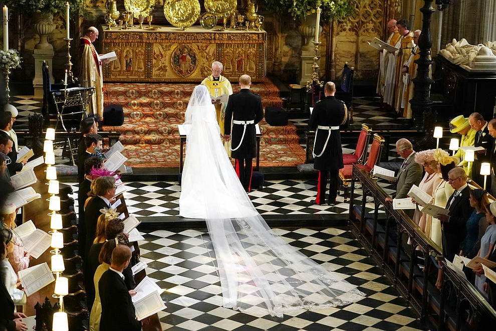 Britain's Prince Harry and Meghan Markle stand in front of Archbishop of Canterbury Justin Welby during their wedding at St. George's Chapel in Windsor Castle in Windsor, near London, England, Saturday, May 19, 2018. (Owen Humphreys/pool photo via AP)