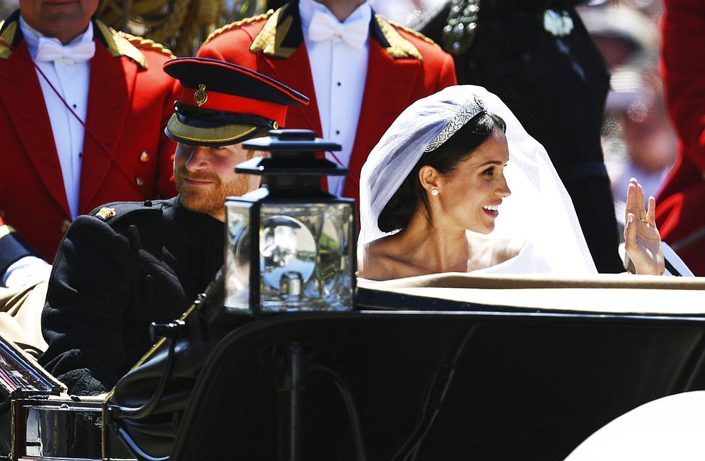 Meghan Markle reacts as she rides in a carriage with her husband Britain's Prince Harry after their wedding ceremony at St. George's Chapel in Windsor Castle in Windsor, near London, England, Saturday, May 19, 2018. (Jeff J Mitchell/pool photo via AP)