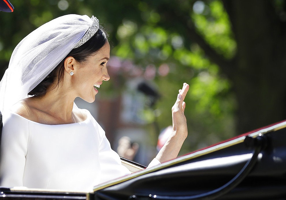 Meghan Markle waves from a carriage after the wedding ceremony of Prince Harry and Meghan Markle at St. George's Chapel in Windsor Castle in Windsor, near London, England, Saturday, May 19, 2018. (AP Photo/Kirsty Wigglesworth, pool)