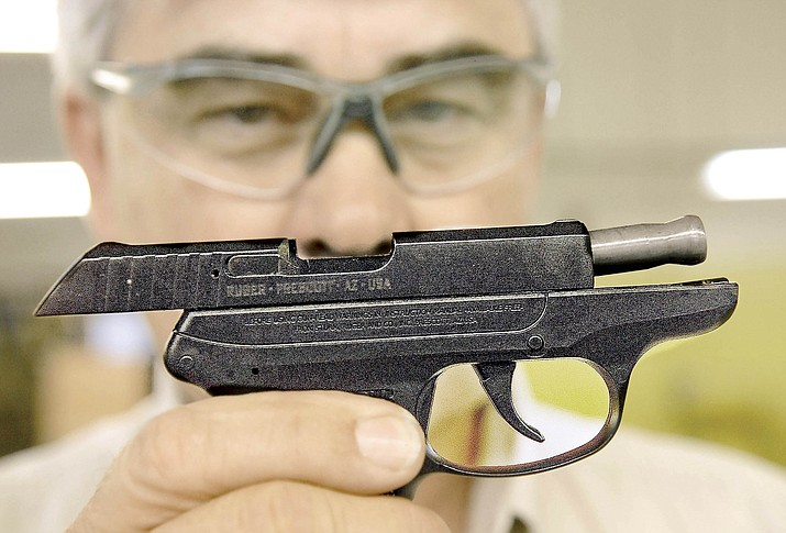 A Ruger Lightweight Compact Pistol (LCP) is displayed in front of James D. Elliott, production manager Wednesday. Ruger is currently being asked by their shareholders to track and report on the gun violence. (Courier file photo)